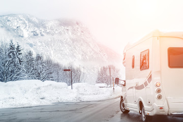 Caravan or campervan turning from road with beautiful mountain alpine landscape on background at...