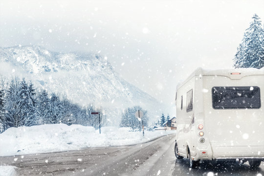 Caravan or campervan turning from road with beautiful mountain alpine landscape on background at cold winter season.Family vacation travel, holiday trip in motorhome. Beautiful austrian nature scene