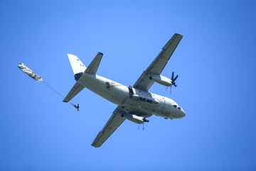 Military paratroopers jump from an Alenia C-27J Spartan military cargo plane.