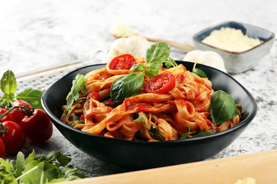 tagliatelle pasta with tomato sauce parmesan basil on rustic background