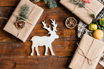 Christmas background with toy deer, packed giftboxes, clementines and decoration