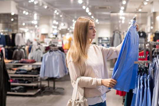 Young casual woman with textile tote bag looking at new blue shirt on hanger