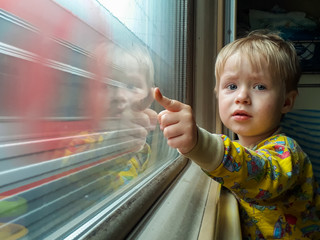 Dad, look - the train! A little blond-haired boy of three years rides on a train, eats candy and looks out the window, behind which a beautiful autumn landscape flies.