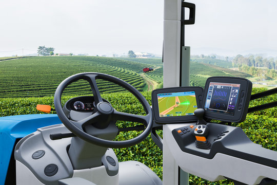 Autonomous tractor working in green tea field, Future technology with smart agriculture farming concept