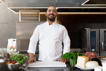 Handsome young African chef standing in professional kitchen in restaurant preparing a meal of meat and cheese vegetables.