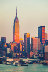 Fototapete - Manhattan skyline illuminated by sunset