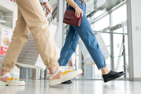 Young woman and her daughter in jeans carrying paperbags while leaving mall