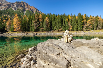 Wall Mural - Autumn time at romantic mountain lake with stone cairns in foreground. Lake Obernberg, Stubai Alps, Tyrol, Austria.