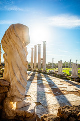 Marble statue under the sun rays and ancient columns at Salamis, Greek and Roman archaeological site, Famagusta, North Cyprus