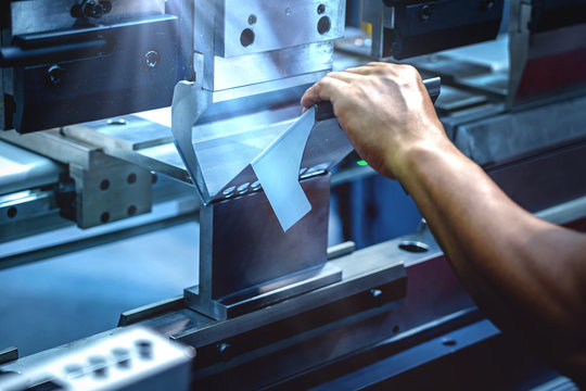Workers bending sheet metal by CNC machines in industrial plants