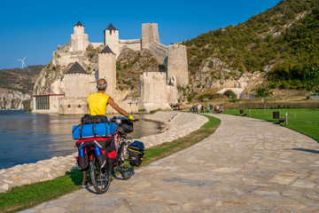 Biker tourist passing by newly restored Golubac fortress in Serbia along the Danube river Fototapete