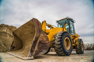 Side view of a yellow bulldozer with dirty metal bucket and black rubber wheels