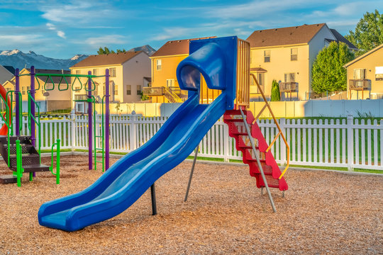 Blue slide with red stairs at a playground against homes mountain and blue sky