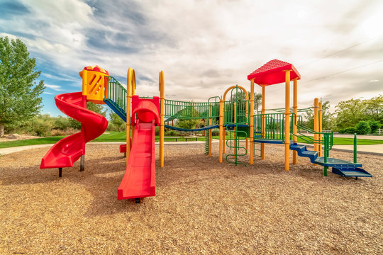 Focus on empty childrens playground at a park with red slides and climbing bars