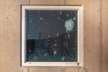 Bullet holes in the window glass of a bulletproof bunker