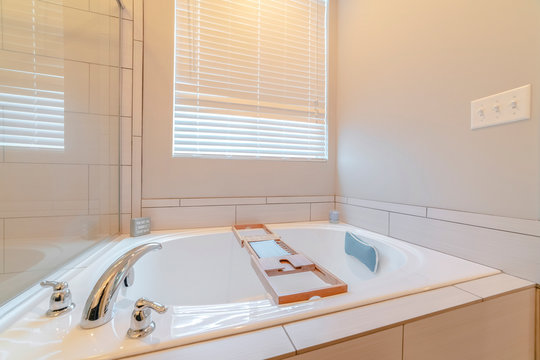 Contemporary spa bath with wooden tray caddy