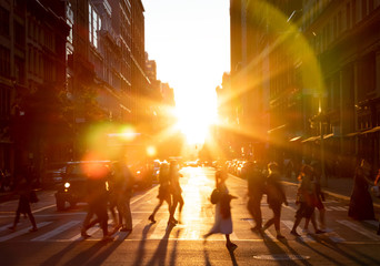 Fotomurales - People walking across the street in New York City with the bright light of sunset shining between the buildings along 23rd St in Midtown Manhattan