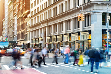 New York City street scene with crowds of diverse people in motion through a busy intersection on 5th Avenue in Midtown Manhattan