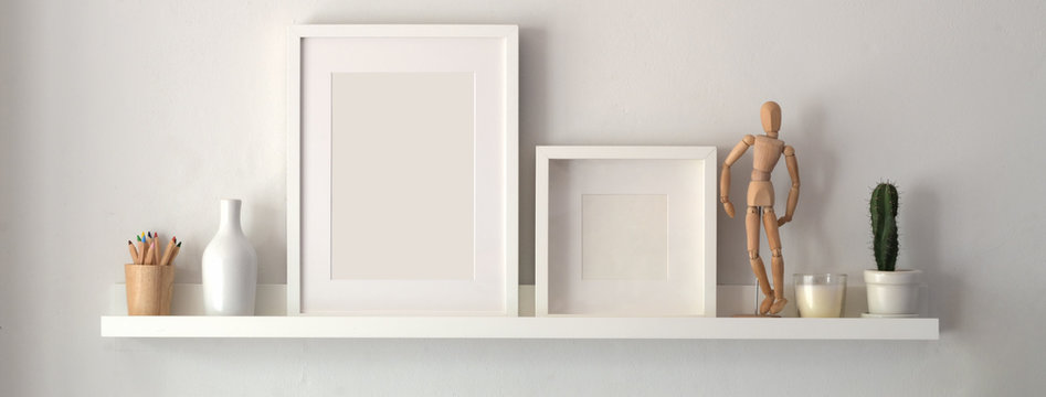 Mock up frame and decorations on shelf with white wall