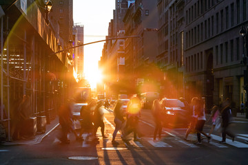 Fotomurales - New York City - Crowds of people walking across the busy intersection on 34th Street with the bright light of summer sunset shining between the buildings of Midtown Manhattan
