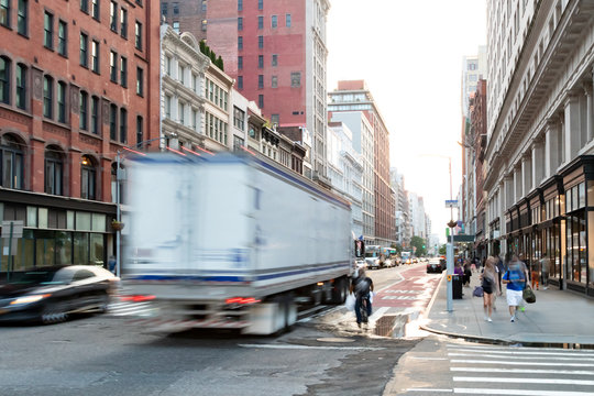 Busy view of 23rd Street with delivery truck speeding past the people walk down the sidewalk in Midtown Manhattan, New York City