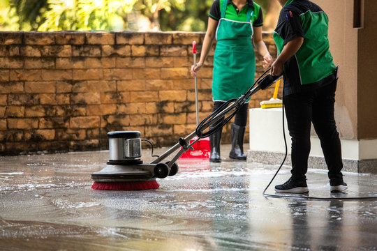 The worker cleaning floor exterior walkway using polishing machine and chemical or acid