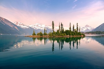 Tuinposter Canada Battleship Island with Pine Trees reflected in calm water of Garibaldi Lake Landscape and Distant Snowcapped Peaks obscured by smoke and ash of summer Wilfdfires in Coast Mountains of British Columbia