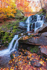 waterfall Shypot of Carpathian mountains in autumn. lake, water. fallen foliage and moss on a massive boulders. rapid water steam. popular travel destination