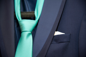 detail of a groom's dark blue costum eand a green tie  - selective focus, space for text