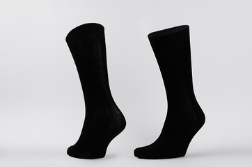 Blank black cotton high socks on invisible mannequin foot as mock up for advertising, branding, design. Front and side view, sportwear template on white background.