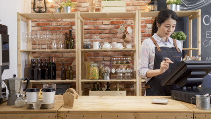 waitress girl in apron using finger touching screen of POS terminal in coffee shop. young woman staff in coffeehouse checking on tablet with software interface to take order and print receipt in cafe