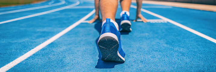 Sprinter fit man waiting for start of race on running tracks at outdoor stadium. Sport and fitness runner athlete on blue run track starting line with running shoes. Banner panorama. Fototapete
