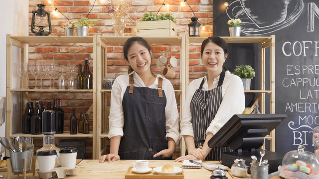 Portrait of cheerful asian female barista laughing during working break together with positive smile. Partnership of youg women in common business cafeteria. two girl staff face camera in coffee shop