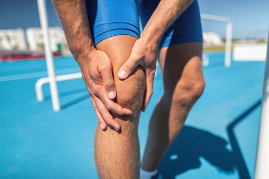 Knee pain professional athlete sport injury - sports running knee acciden on man runner. Sprained knee joint, arthritis. Closeup of legs, muscle and knee outdoors.