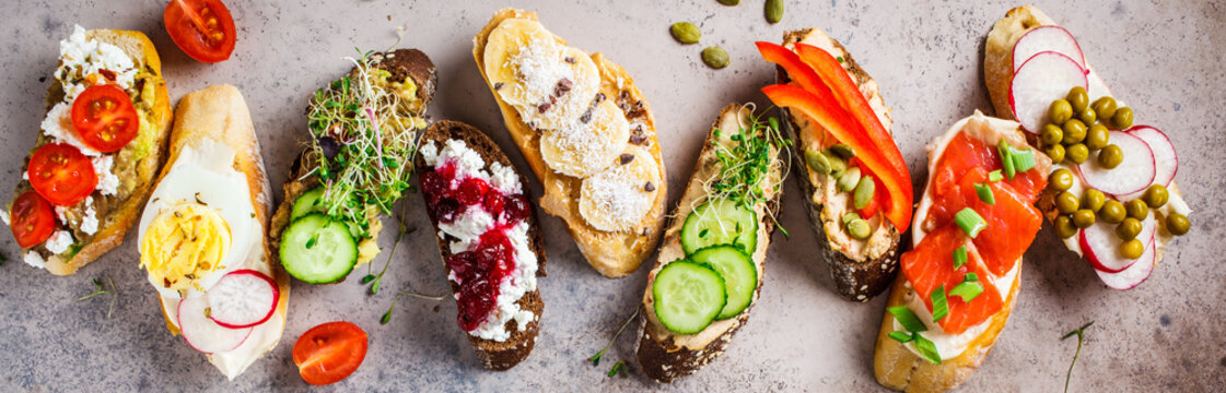 Open toasts with different toppings on gray-brown background, top view.  Flat lay of crostini with banana, pate, avocado, salmon, egg, cheese and berries.