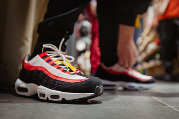 Side view of bright sneakers with black and red stripes on crop person bending to tie shoelaces on floor
