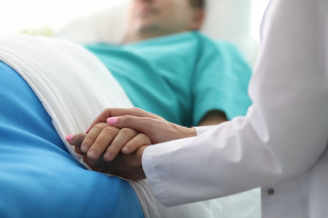 Female doctor hands hold male arm in medical hospital