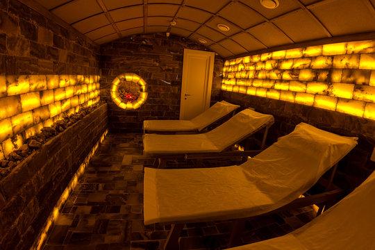 Interior relaxation salt room on dark orange illumination in medical spa salon