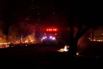 A fire engine drives on a road with active fire on both sides during the wind-driven Kincade Fire in Santa Rosa, California