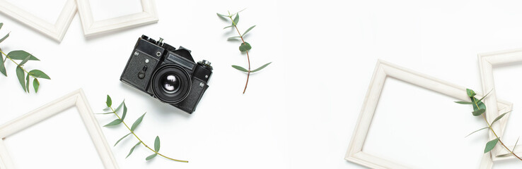 White photo frame, old retro photo camera and green eucalyptus leaves on white background. Flat lay top view copy space. Stylish minimal composition, artwork mockup, picture frame, home decoration