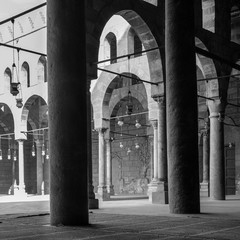 Black and white shot of corridors surrounding the courtyard of public historical Mosque of al Sultan al Nasir Muhammad Ibn Qalawun situated in the Citadel of Cairo, Egypt