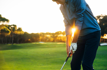 Male golf player teeing off golf ball from tee box to beautiful sunset Wall mural
