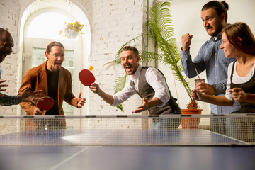 Young people playing table tennis in workplace, having fun. Friends in casual clothes play ping...