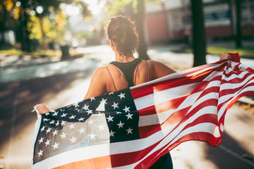 Athletic young woman running with american flag.