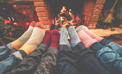Legs view of happy family lying down next fire place wearing warm wool socks - Winter, holiday, love and cozy concept - Focus on feet