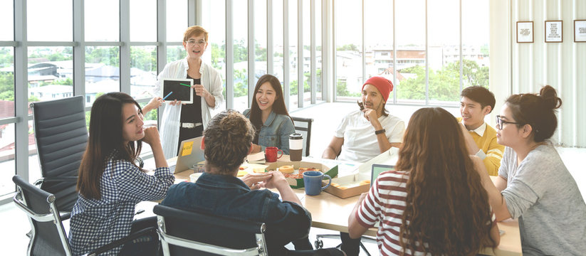 Young multiethnic diverse creative asian group talking or brainstorm in office meeting workshop with technology. Happy young student asian or college marketing team spend coffee break time together.