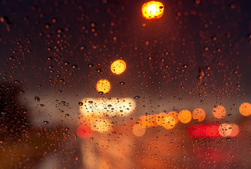 Orange night light bokeh from street light on traffic jam day. Rainy day. Transparent glass window with rain drop. Romantic weather. City life. Blur abstract background of urban light on rainy season Fotomurales