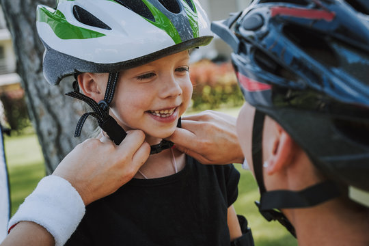 Loving mother helping her daughter to put on bicycle helmet