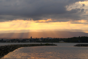 Yellow colored sunbeams during sunset at the Lake Geneva from park Vidy in Lausanne, Switzerland