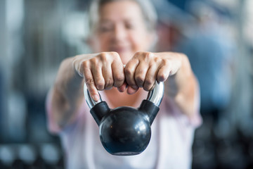 close up of senior holding a weight with his hands in front of the camera at the gym - adult woman working his body to be healthy Wall mural